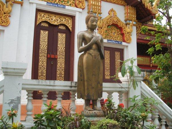 (佛塔底部) 广场上大榕树下的佛像,旁边的桌椅是僧人们和游客交流的